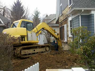 The backhoe excavating for the new foundation