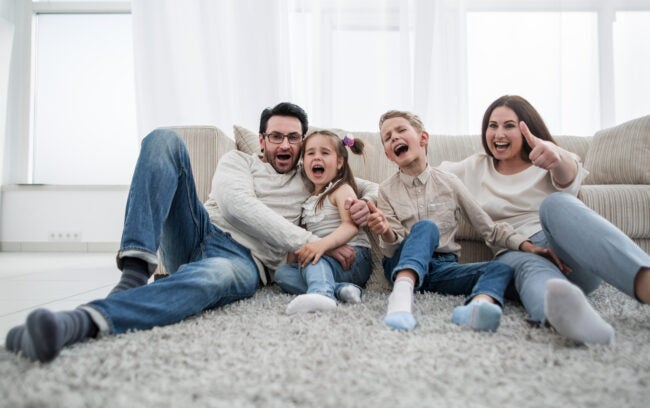 happy family sitting on the carpet in the living room.the concept of family happiness