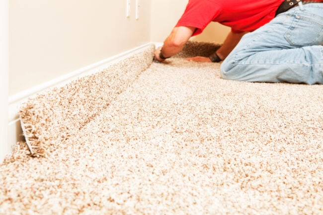 Bedroom Carpet Installation with Worker Cutting