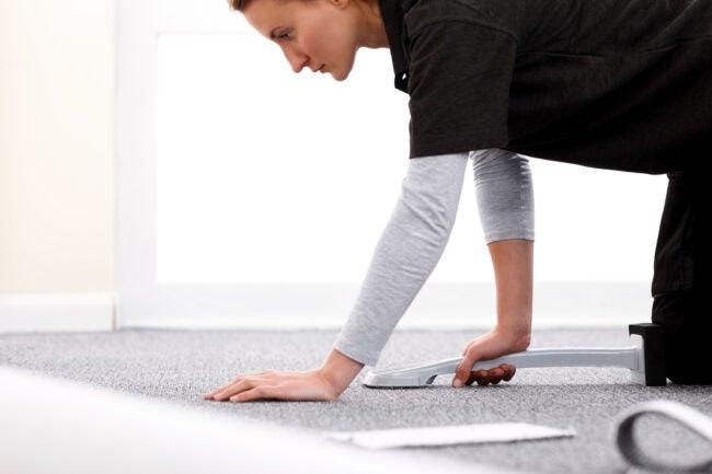 Female installer using a knee kicker to stretch carpet