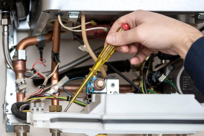 Technician repairing the combi gas boiler with Screwdriver in hand