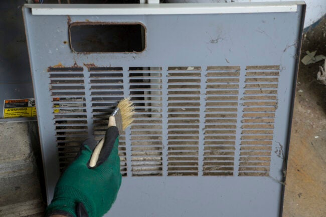 Technician cleaning the front cover os a gas furnace before re-installing .