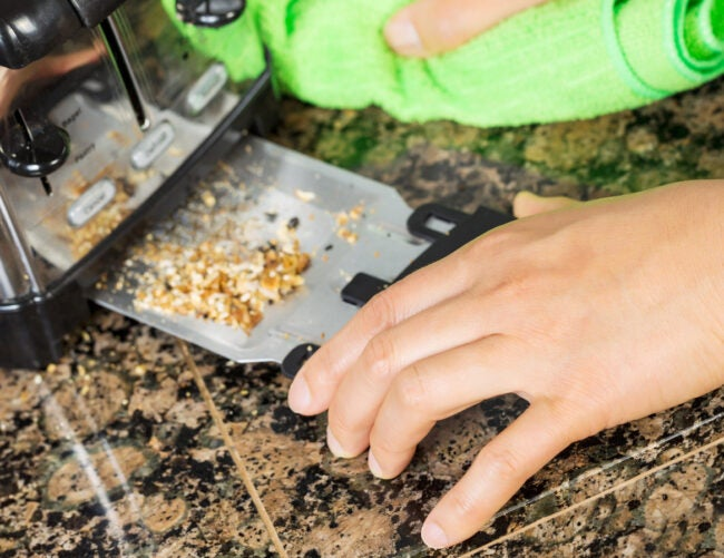 Photo of female hand cleaning bottom of kitchen toaster tray with green microfiber rag with stone counter top in background