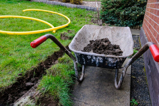 Wheelbarrow full of soil after a trench has been dug at the bottom of a lawn to install a drainage channel.