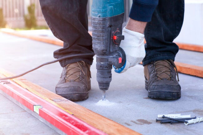 hammer drill drilling hole in concrete