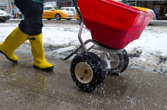 Person in yellow boots using ice melt