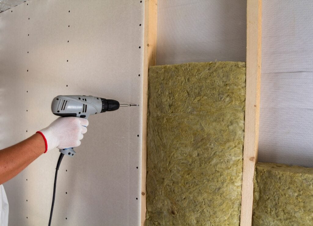 Close up of worker with electric screwdriver fastening drywall