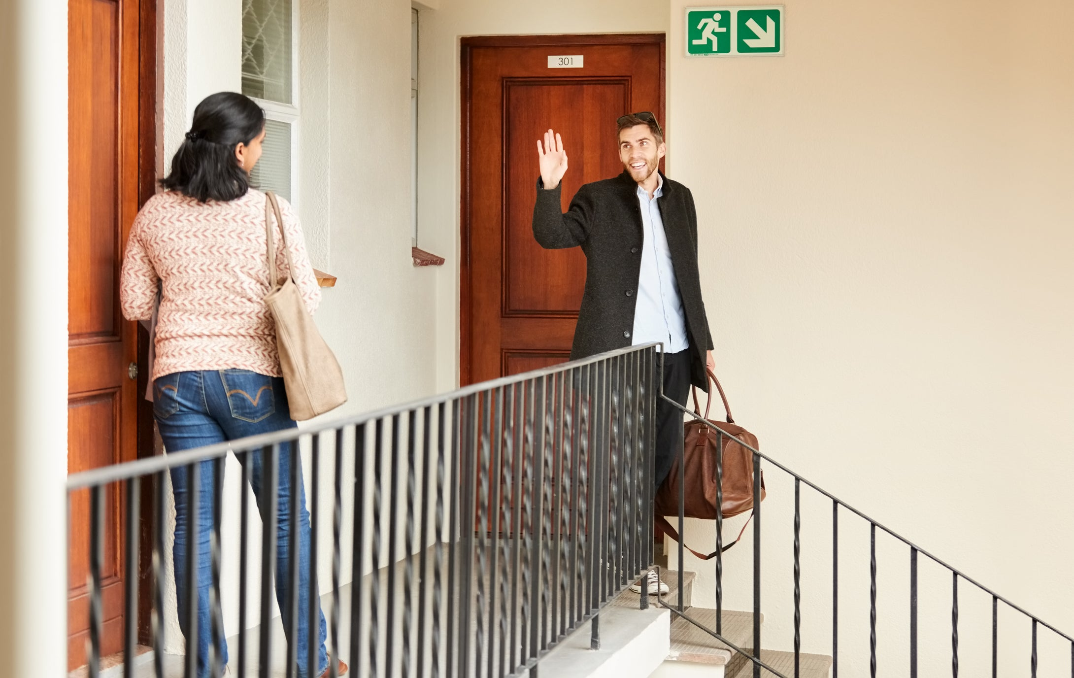Shot of a man going out and waving to the female neighbour