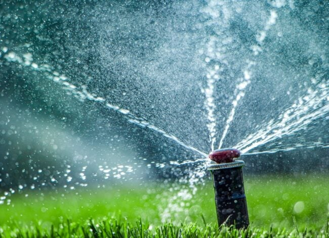 automatic-sprinkler-system-watering-the-lawn-closeup-picture-id1201306662