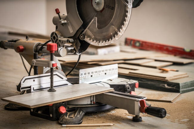 sliding compound miter saw cutting flooring