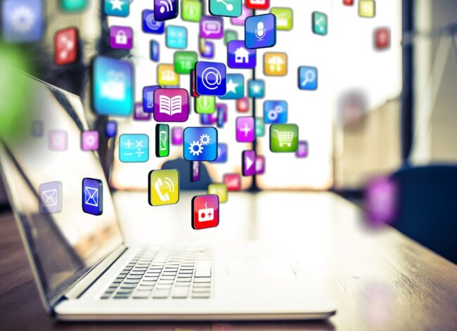 multicoloured-applications-flying-out-or-into-a-laptop-picture-id882299064