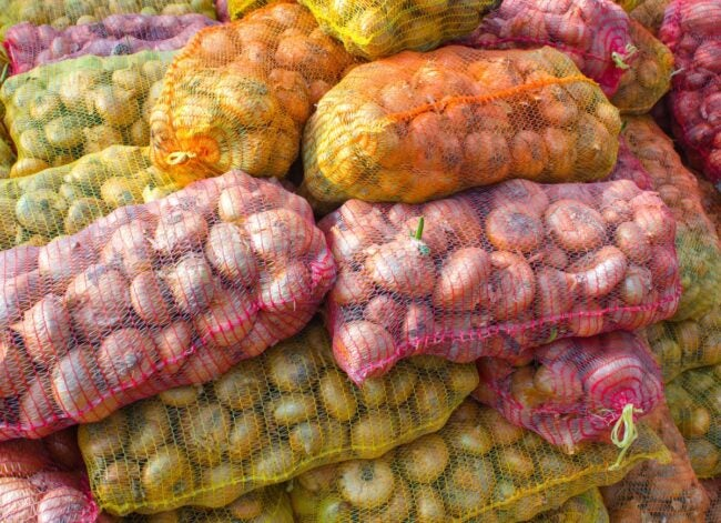 onions-in-yellow-and-pink-plastic-mesh-sacks-picture-id905268184