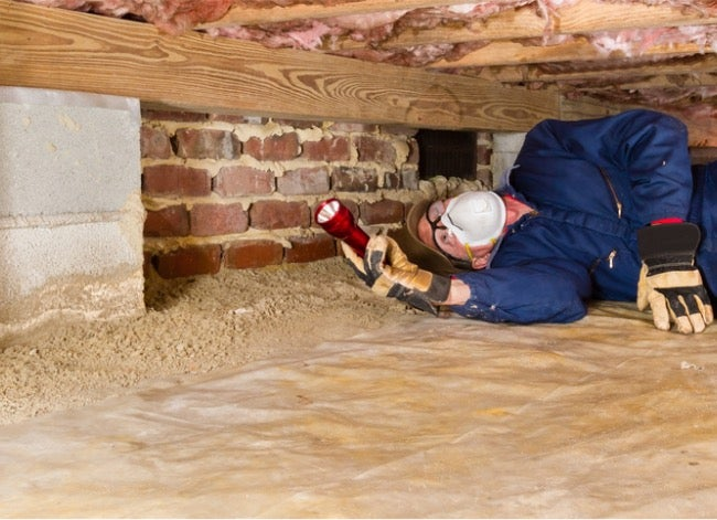 home inspector looking under house