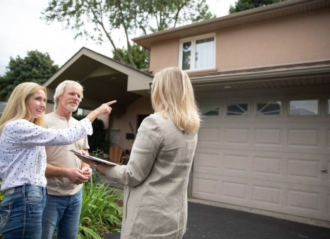couple with real estate agent looking at house
