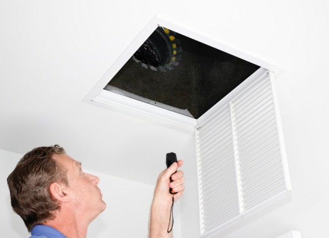 home inspector looking inside vent