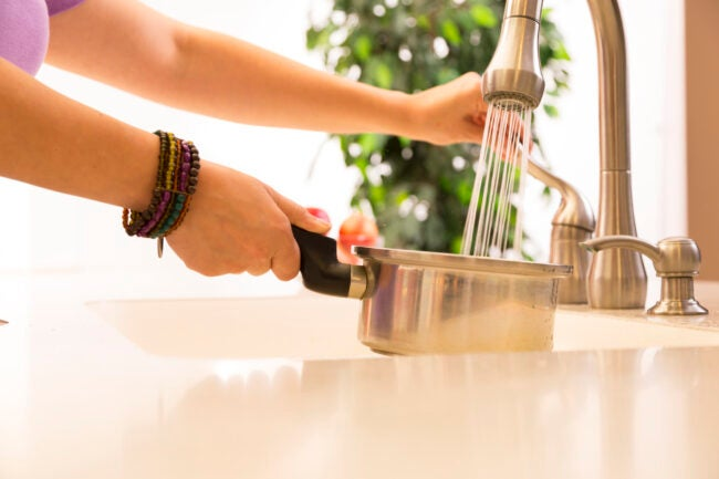 Woman putting water in small cooking pot at the kitchen sink. Spray running water from the faucet.