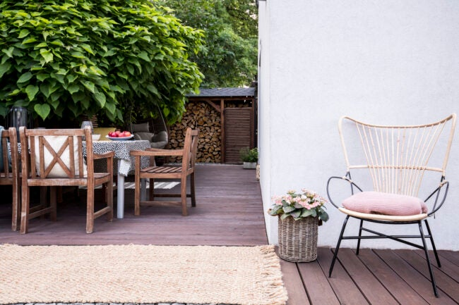 Pink flowers next to armchair on wooden terrace with chairs at table next to tree