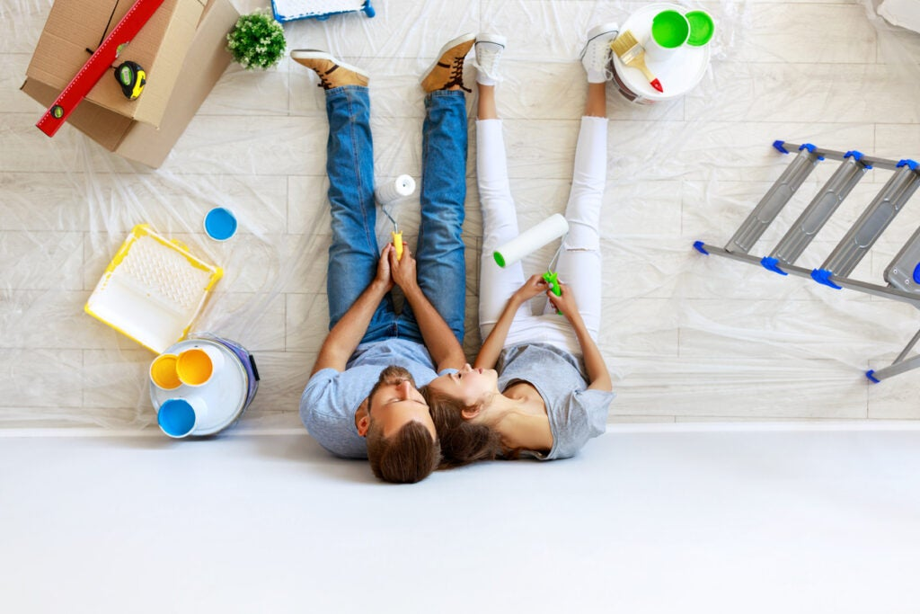 young tired couple is repairing and painting the wall at home