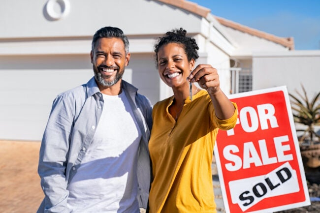 couple holding keys to new home