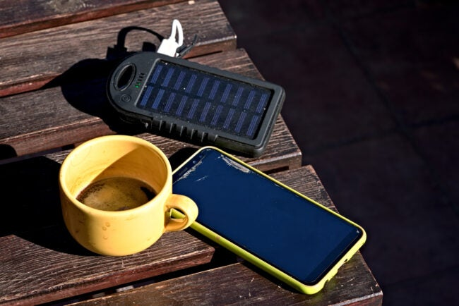 smartphone, power bank and a cup of coffee on the porch