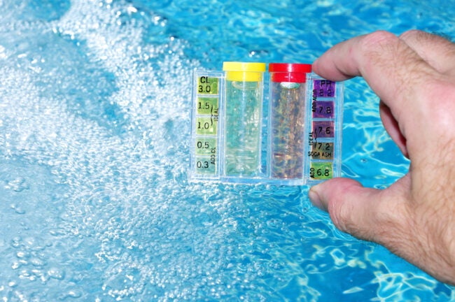 A hand holding a water test kit with pool water background.