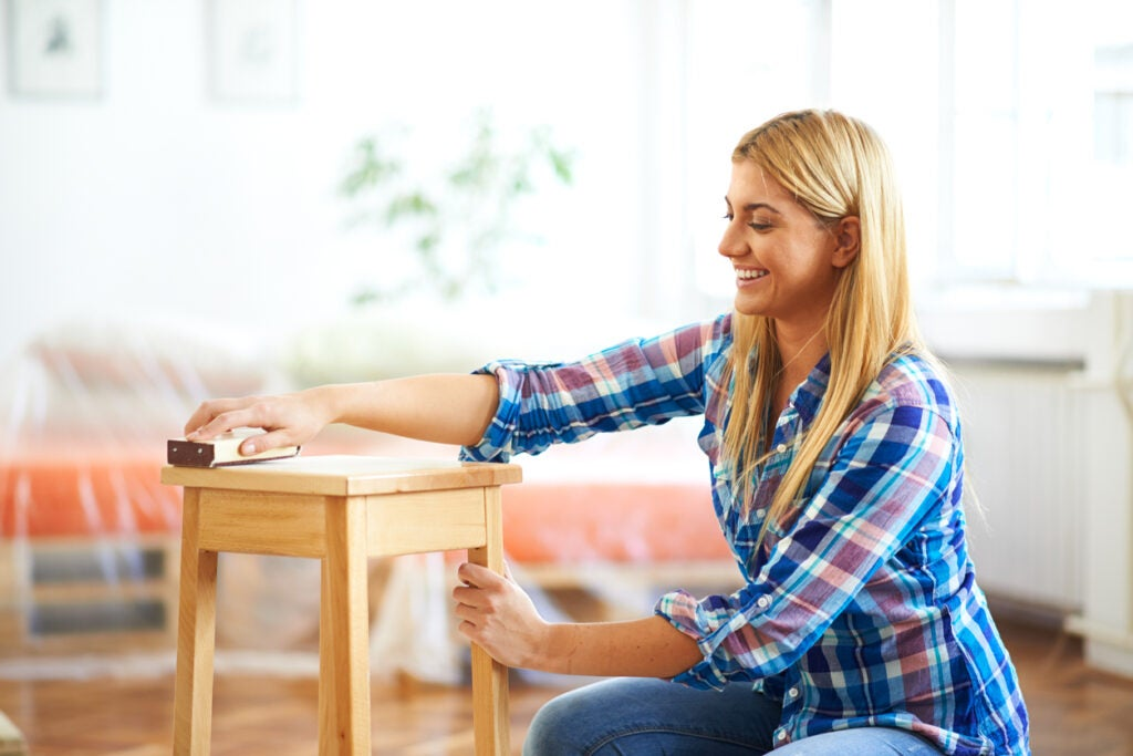 Woman is sanding wooden furniture.