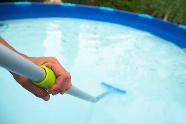 closeup of a young caucasian man cleaning the bottom of a portable swimming pool placed in the backyard with a brush mounted in a telescopic pole