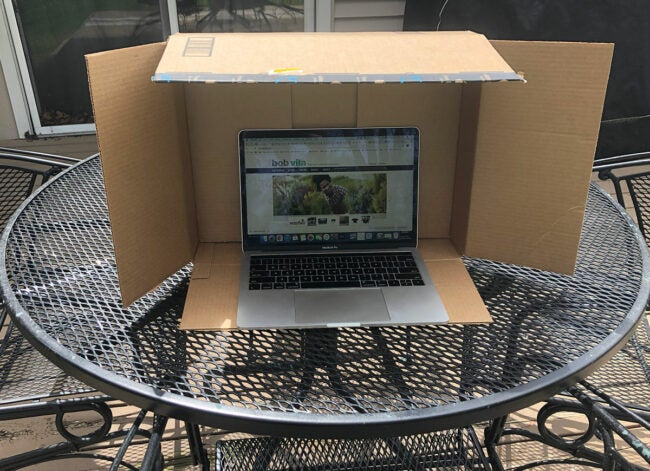 using cardboard box to shade computer glare when working outside