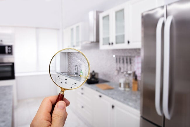Close-up Of A Man's Hand Holding Magnifying Glass Over The Kitchen In Modular Kitchen