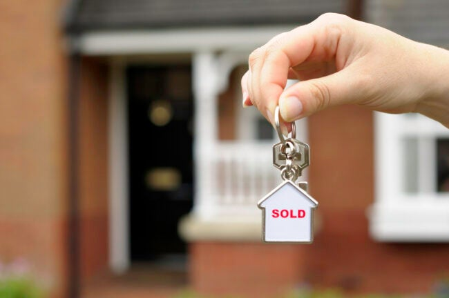 New home concept portrayed by a female holding front door keys in front of a newly built house.