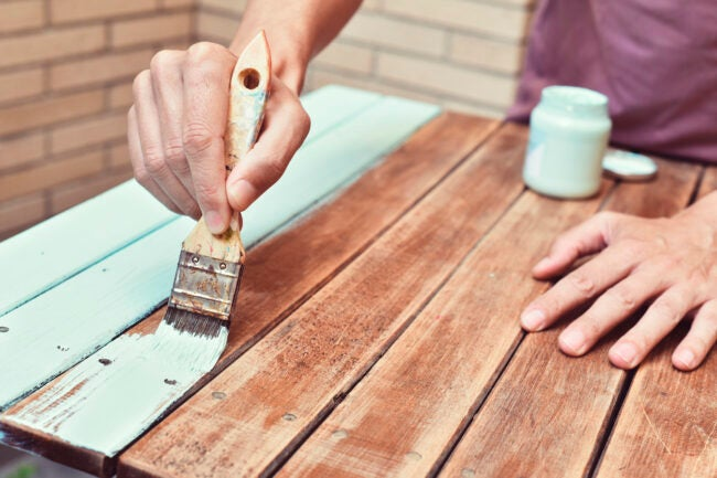 closeup of a young caucasian man painting an old wooden table with a brush