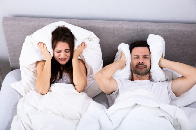 Disturbed Couple Covering Their Ears With Pillow On Bed