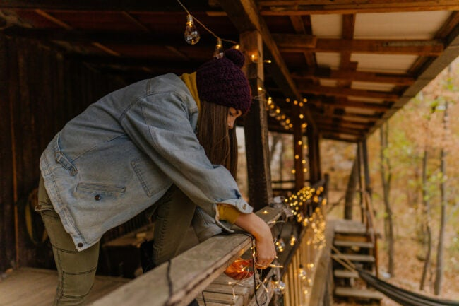 Photo of a young woman decorating the balcony of her log cabin in the woods.