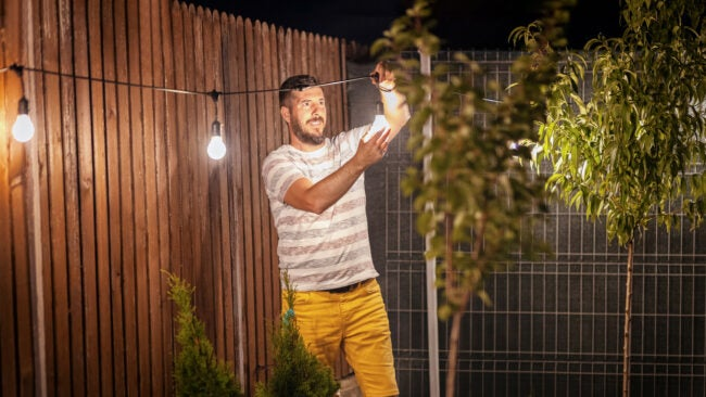 Party time in backyard with happy millennial man hanging string lights in trees – Weekend summer night mood with smiling guy arranging the light garland for outdoor dinner party in home garden
