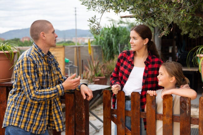 Young attractive woman with daughter and positive man talking on the border of the garden plot
