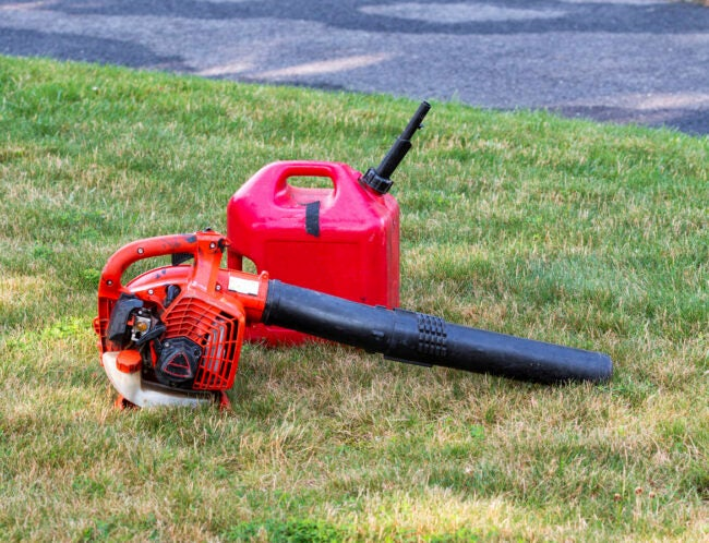 A landscapers leaf air blower with a gas can lying on the ground of a residential green grass lawn.