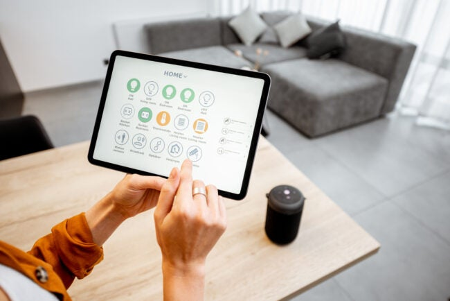 Young woman controlling home with a digital touch screen panel. Concept of a smart home and mobile application for managing smart devices at home